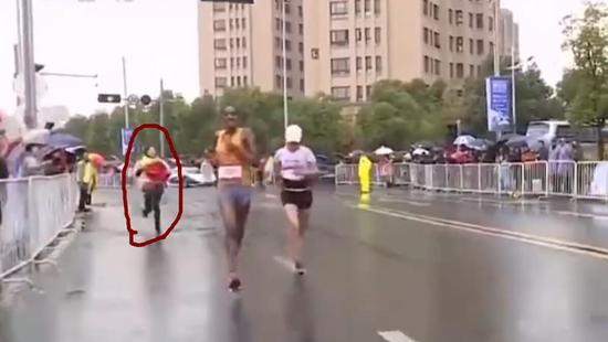 第一名志愿者冲上去为何引丽递国旗,但无奈速度没跟上。